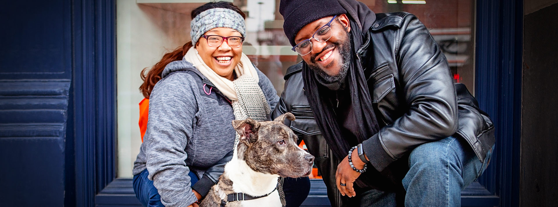 Woman in gray jacket and man in black jacket squatting next to white and brindle pit bull type dog