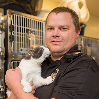 Nate Beckstead, an animal control officer, holding a white and gray cat