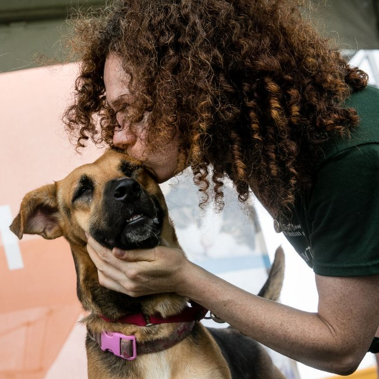A woman with curly hair kisses a dog on the cheek