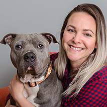 Smiling woman hugging a gray pit bull terrier