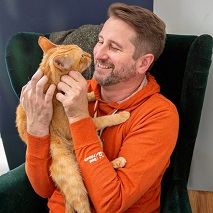 Guy in orange sweatshirt holding orange cat