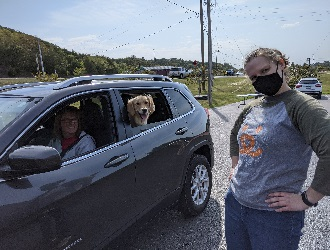 Woman in gray sweatshirt standing next to car with white dog in back seat
