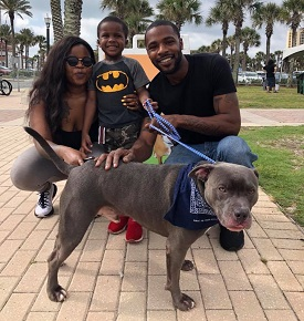Couple with young son with gray pit bull on brick walkway