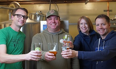 Four people with glasses of beer at brewery