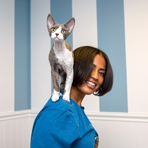 Woman in blue shirt with white and gray cat standing on her shoulder