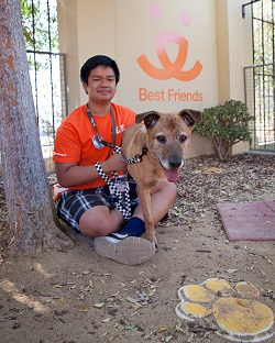 Young man in orange shirt in sitting in front of BF building with brown dog