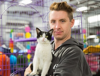 Man holding black and white cat in front of cage