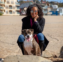 Woman wearing sunglasses crouching behind brown pit bull type dog on the beach