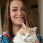 Elise Traub holding an ear tipped long haired creamsicle cat