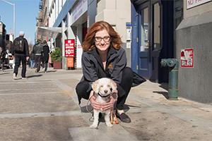 Elizabeth Jensen on a street holding a dog