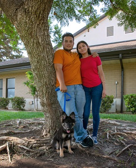 Man and woman standing in front of tree with black and brown German shepherd puppy