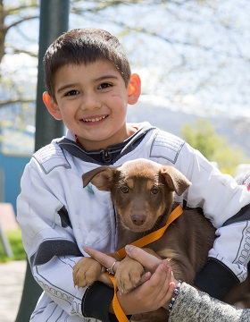Young boy in black and white shirt holding brown puppy