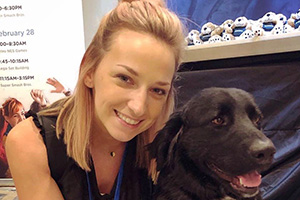 Kayla Sebo posing with a black dog
