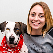 Kristan McCormick with brown and white dog wearing a red bandana