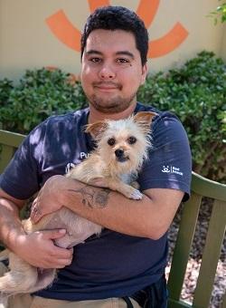 Man in dark tshirt holding small tan dog