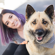 Woman with purple hair and a shepherd-type dog