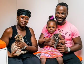 Couple with young daughter holding two kittens