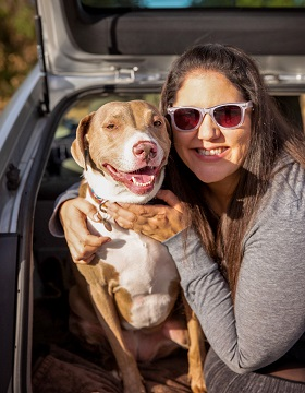 Brown dog and woman in gray sweatshirt and sunglasses sitting in back of car