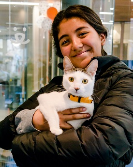 Young woman with long dark hair wearing dark coat holding cat
