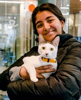Woman in black coat holding white and tabby cat