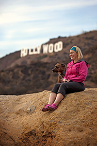 Peggy Kennedy with a dog in front of the Hollywood sign