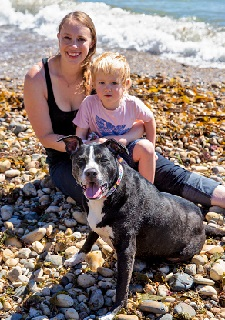 Blond woman in dark tank top with little girl in pink shirt on beach sitting with black and white pit bull type dog