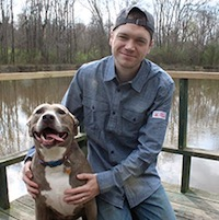 Nick Walton posing with his dog on a dock next to a lake