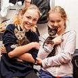 Two blonde girls holding kittens