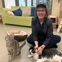 Trish Tolbert sitting on the floor with two cats
