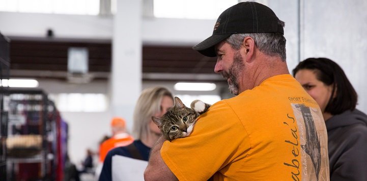 Man in black hat and yellow shirt cradling tabby cat looking at camera