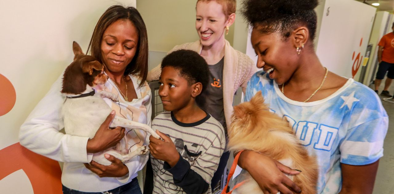 A family of three and an adoption counselor hold two dogs at the Best Friends Lifesaving Center in Atlanta