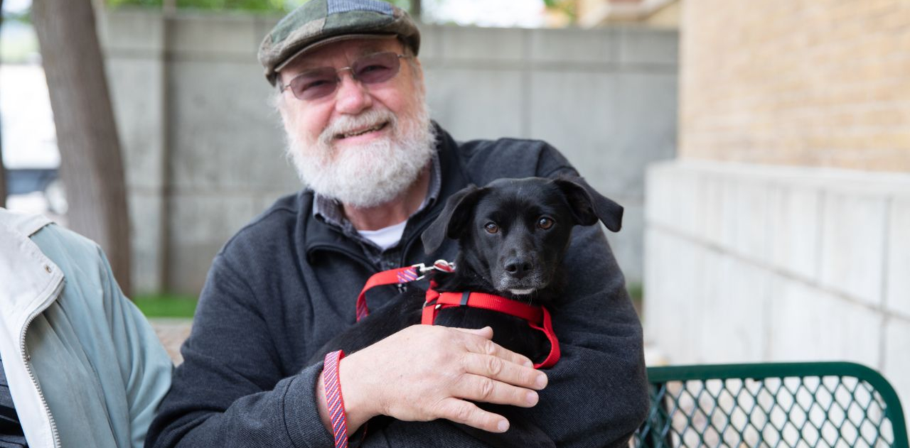 A man with a hat, glasses and white beard sits on a bench while holding a newly adopted black dog wearing a red harness and leash
