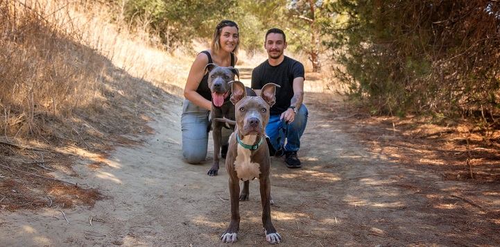 Couple kneeling on trail with two dogs in front