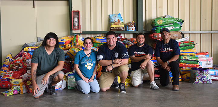 Group of people sitting in front of a large pile of donated items