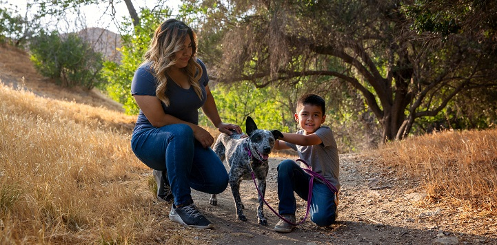 Woman and young boy crouching on gravel path with black and white dog