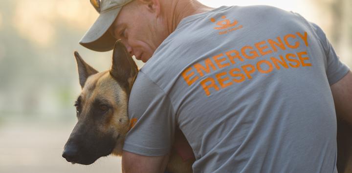Tan dog being held by man in grey emergency response shirt