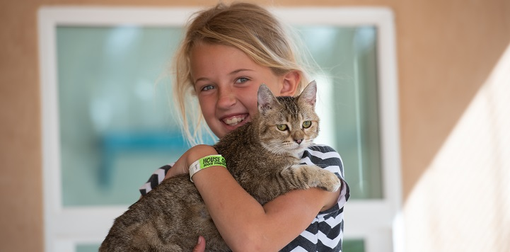 Young girl in black and white top holding tabby cat.
