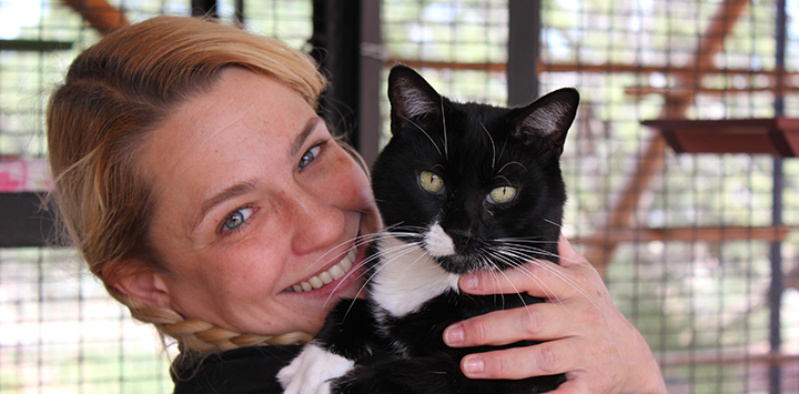 Woman holding a black and white cat