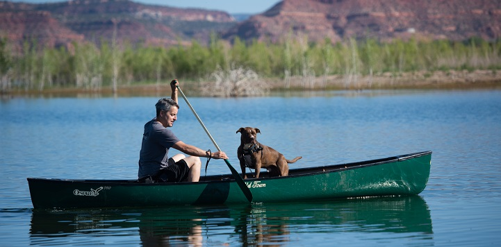 Man and dog in green canoe on water with mountains in background
