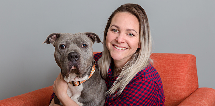 Smiling woman sitting on an orange chair with a gray pit bull terrier on her lap