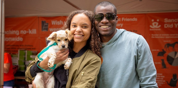 Man in gray sweatshirt standing next to woman in green jacket holding small dog