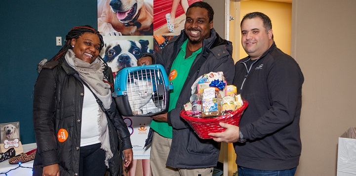 Woman standing next to man holding white cat in blue carrier next to a man holding a red gift basket