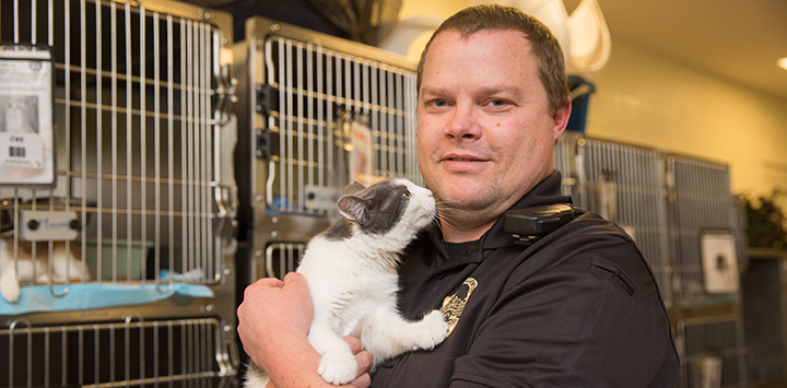 Animal Control Officer Nate Beckstead holding a cat in front of kennels