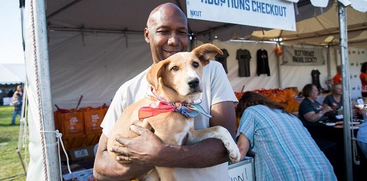 Smiling man in gray shirt holding tan dog wearing orange bandana in front of adoption booth