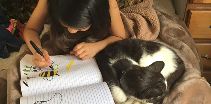 Black and white cat curled up next to little girl with dark hair writing