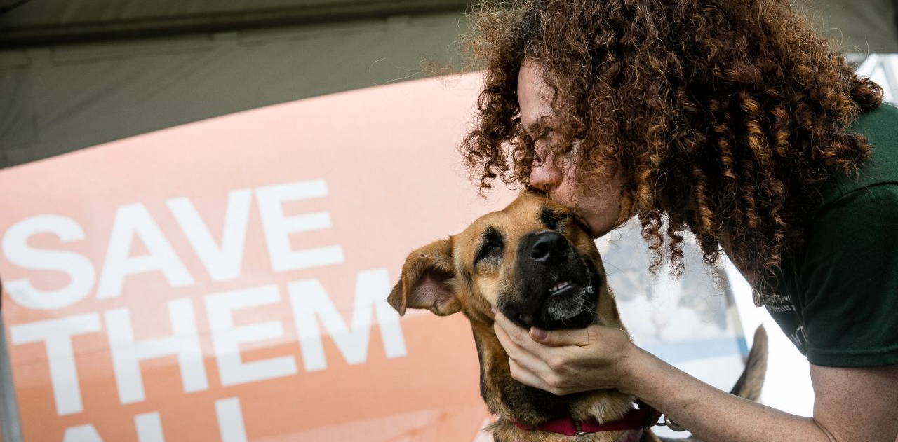 A woman with curly hair kisses a dog on the cheek in front of a Save Them All banner