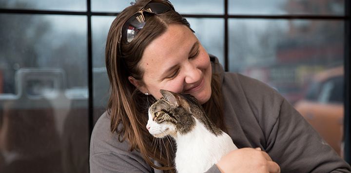 Woman cradling cat she's being reunited with
