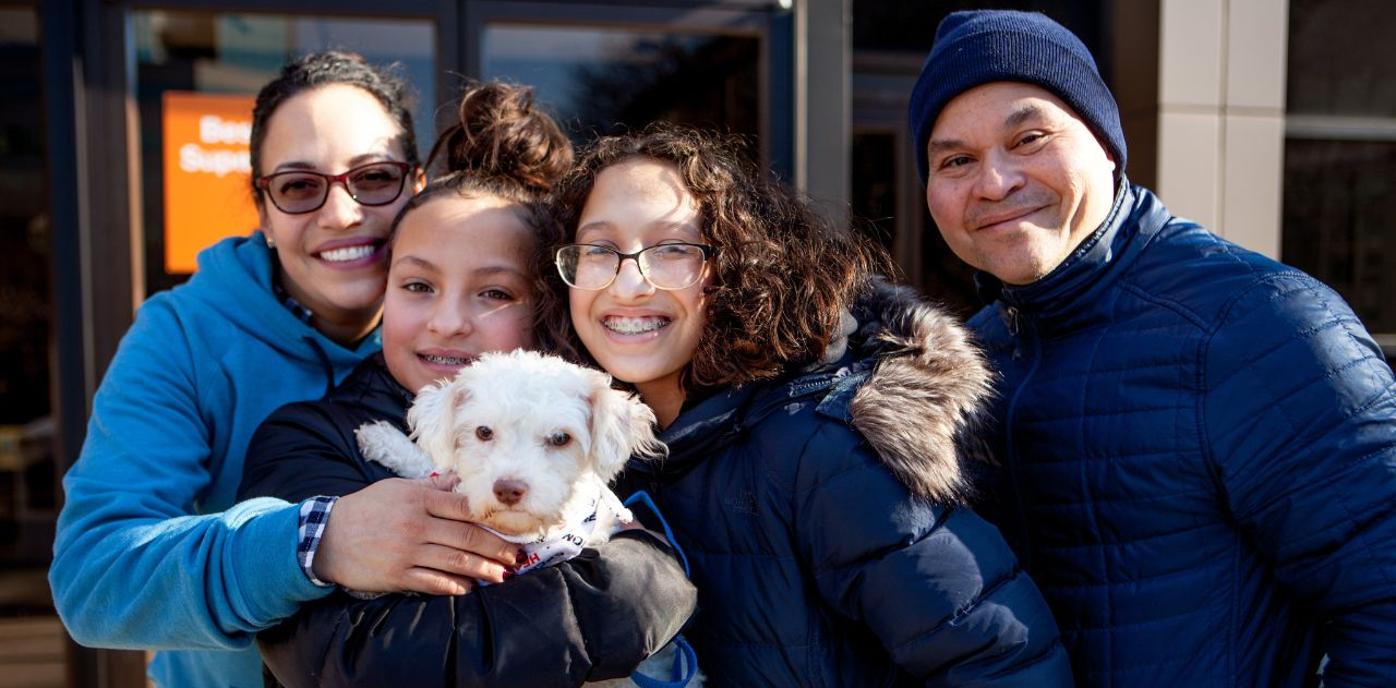 A family of four people holds a small white dog at an adoption event