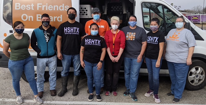 Nine people with masks standing in front of the side of open Best Friends transport van