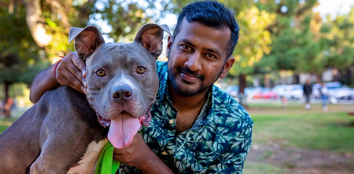 Man in teal multi colored shirt sitting with dark gray pit bull type dog